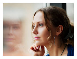 Woman looking through window and contemplating
