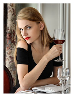 Woman at restaurant enjoying glass of wine