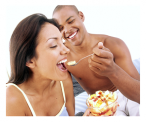 Young Couple Sharing Food in Bed