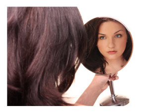 Young Woman Looking at Herself in Mirror