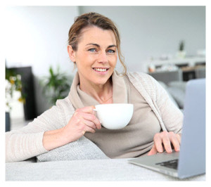 Woman Blogging at Laptop with Coffee