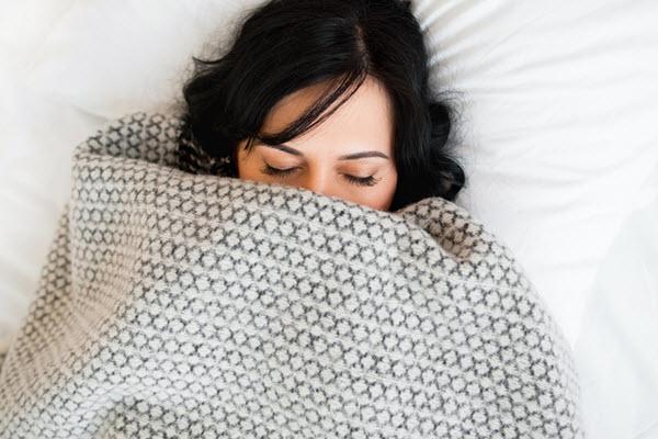 Woman Snuggled Under a Blanket Sleeping 600