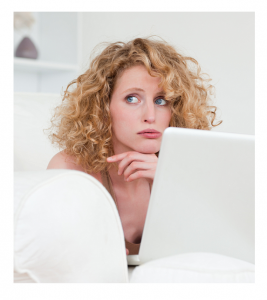 Woman at laptop in bed with worried expression