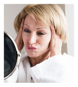 Mature Woman Making a Face Looking in the Mirror