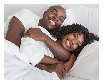Happy African American Couple Snuggling in Bed