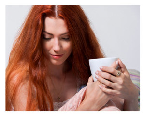Pensive Redhead Having Coffee in Bed