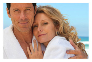 Happy Mature Couple at Beach in Bathrobes