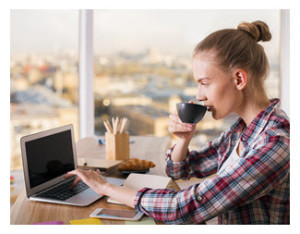 Woman Drinking Coffee and Writing on Laptop